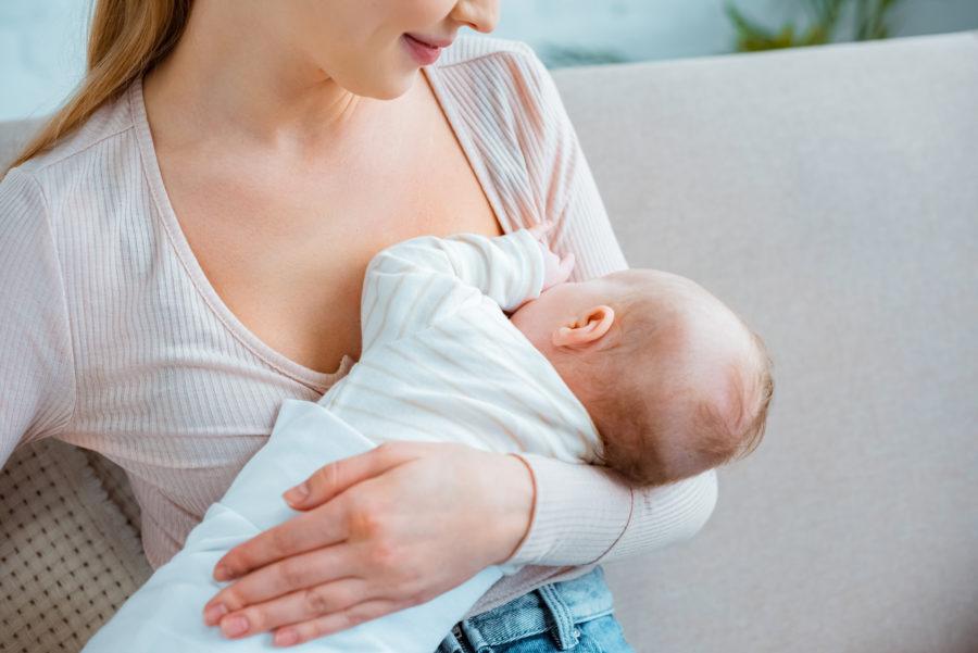 Mãe amamentando seu bebe e provendo a alimentação no primeiro ano de vida