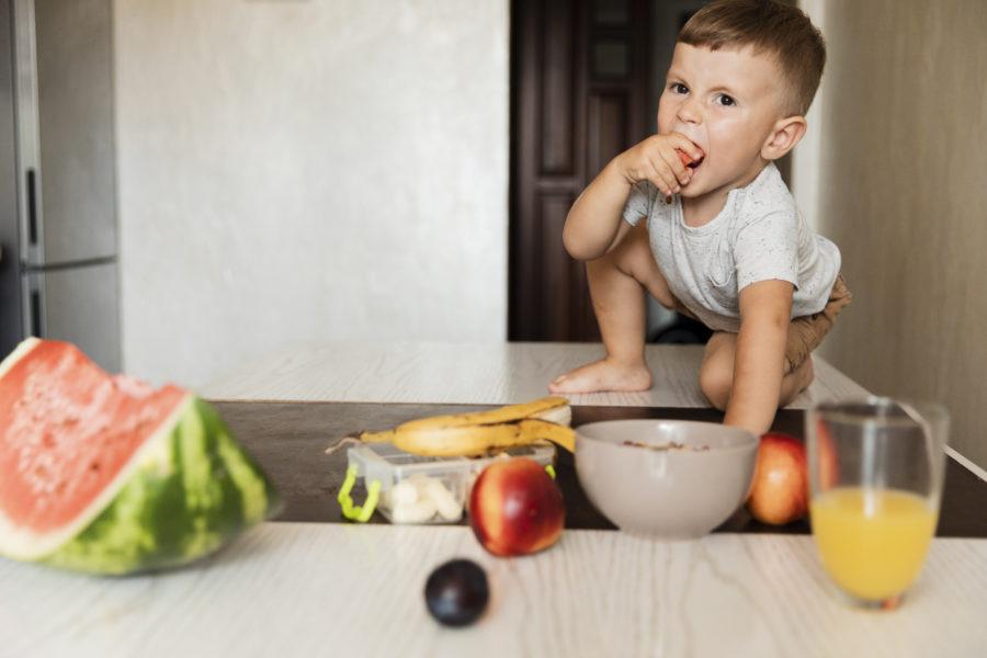 Menino hiperativo com dificuldade alimentar proveniente do TDAH em cima de uma mesa repleta de alimentos saudáveis