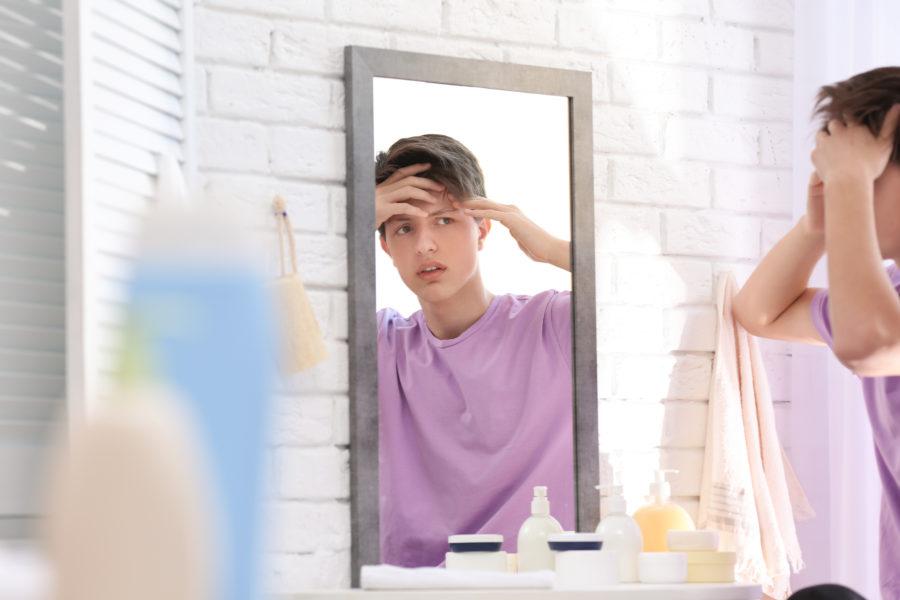 Adolescente menino se olhando no espelho a com as mãos na testa à procura de acne