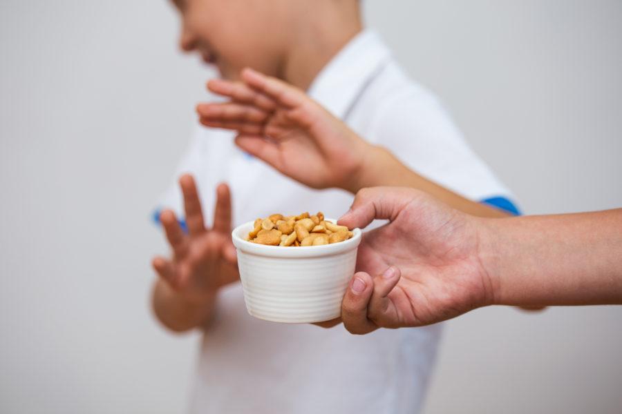 Close de uma mão com um pote de amendoim enquanto, ao fundo, um garoto desfocado rejeita o alimento por ter alergia alimentar