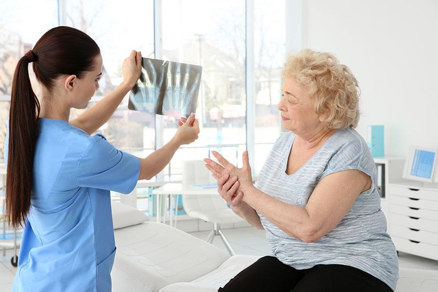Médica está olhando o raio X das mãos de uma senhora enquanto ela está na cadeira segurando suas mãos com dor por causa da artrose