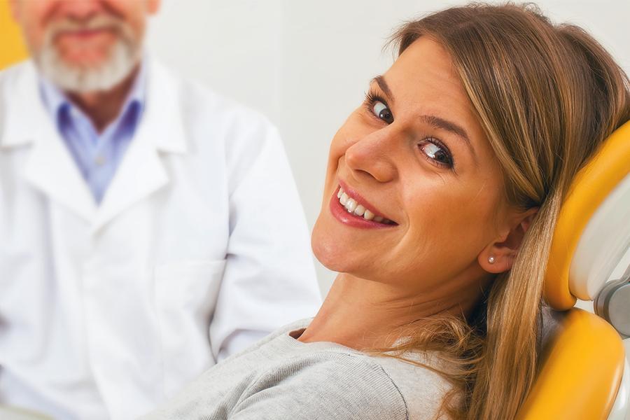 Mulher sorrindo em uma cadeira de dentista com o dentista ao fundo desfocado