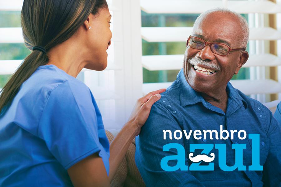 Idoso sorrindo sendo atendido em casa por uma médica mulher e ao lado dele sua esposa com os dizeres novembro azul
