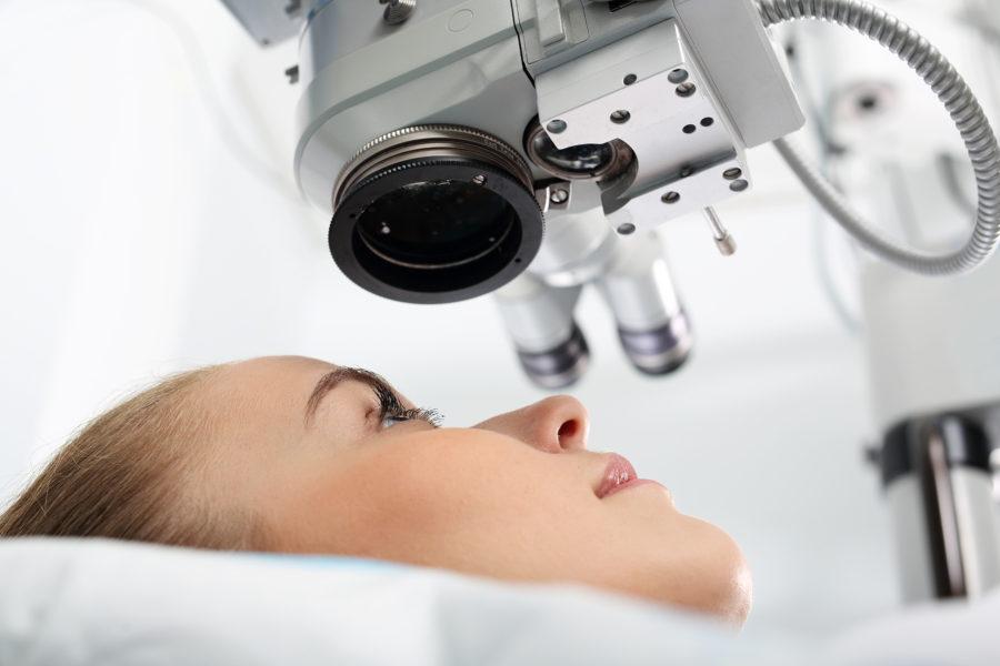 Vista de baixo pra cima do rosto de uma mulher com um aparelho de cirurgia ocular à laser apontado para o seu olho