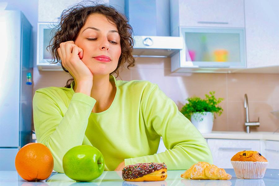 mulher que sofre de compulsão alimentar em uma cozinha olhando para diversos alimentos