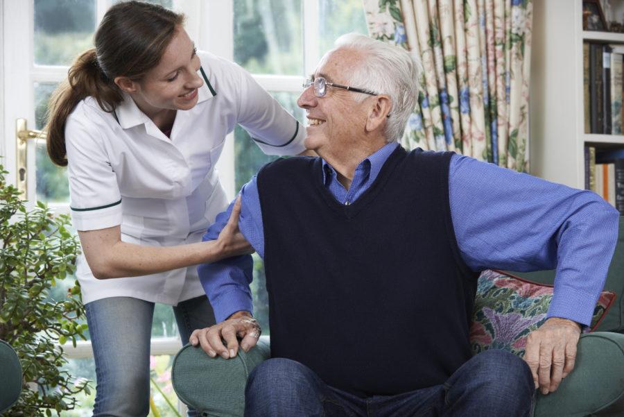 Homem idoso recebendo cuidado de médica mulher em casa