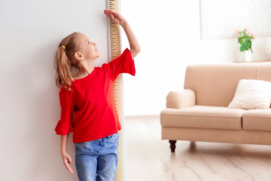 Menina pequena medindo seu tamanho em uma régua na parede para ver seu crescimento infantil