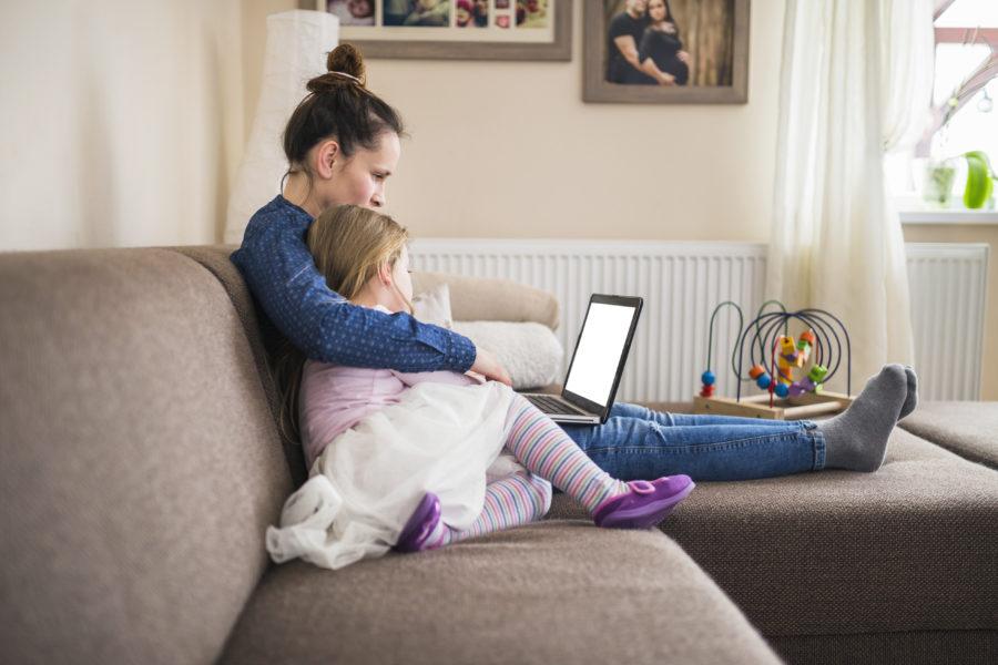 Mãe e filha abraçadas no sofá de casa mexendo no computador representando o uso da tecnologia na infância