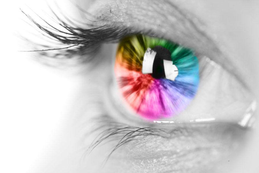 Close de um olho com a Iris colorida de várias cores e restante do olho preto e branco para representar o daltonismo