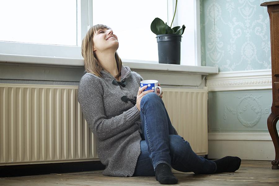 retrato de uma mulher relaxando em casa com uma xícara de chá