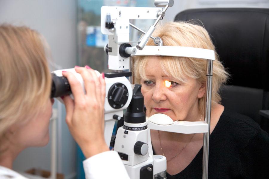 Oftalmologista fazendo o exame de Degeneração Macular Relacionada à Idade (DMRI) em uma paciente idosa