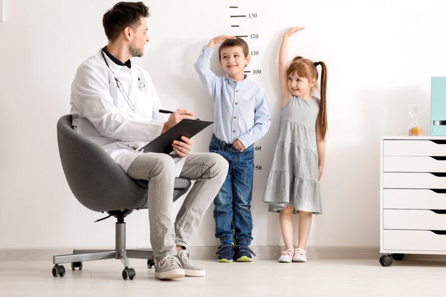 Médico com uma prancheta sentado em uma cadeira medindo a altura de duas crianças por meio de marcações na parede