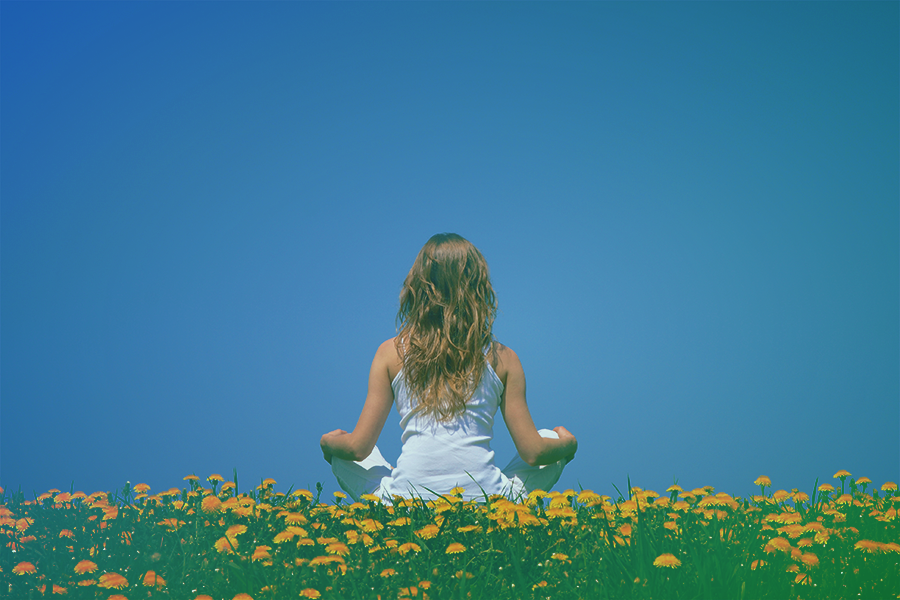 mulher setada de pernas cruzadas ao ar livre praticando o detox emocional