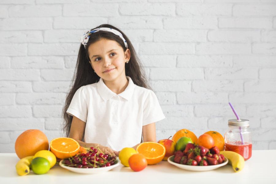 Menina com cara duvidosa atras de uma mesa com alimentos saudáveis. Esses alimentos são parte das dietas saudáveis