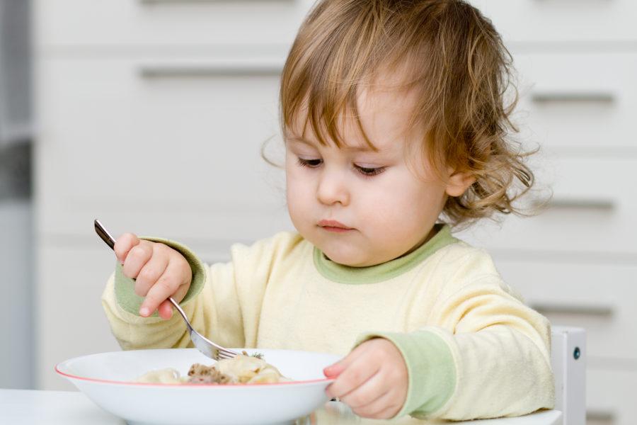 Criança pequena comendo na tigela com garfo, usando o eixo cérebro-coração