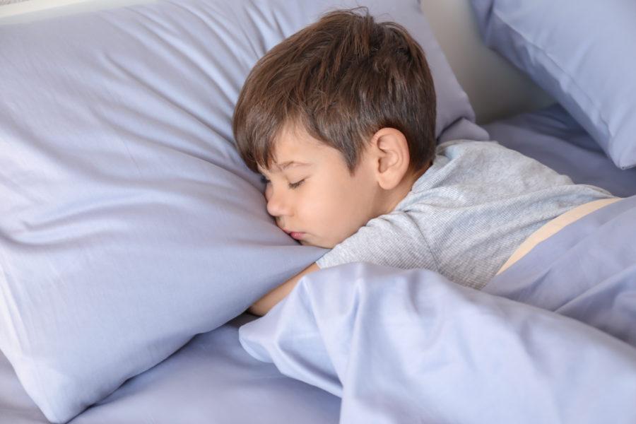 Garoto com sono dormindo de barriga pra baixo na cama