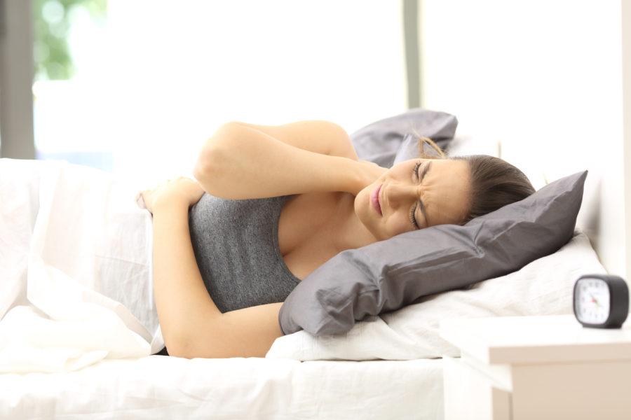 Mulher com fibromialgia deitada com as mãos no pescoço que está dolorido e na barriga para simbolizar a microbiota intestinal e o rosto com semblante de sofrimento.