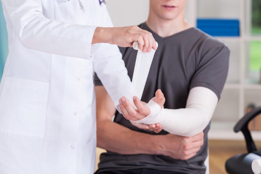 Médico enfaixando braço de um homem devido a fratura do escafóide