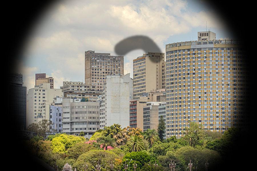 Simulação da visão com glaucoma. A visão é de uma cidade com prédios e árvores. As bordas estão escuras e no meio tem um forma cinza com um pouco de transparência em forma de uma minhoca