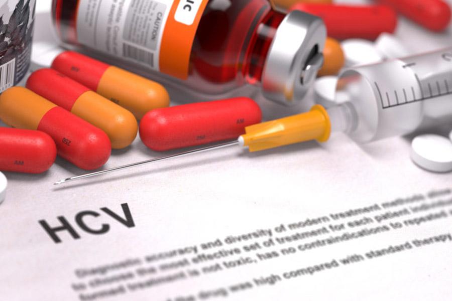 Diagnóstico de hepatite com pílulas, seringa e frascos com líquidos em cima
