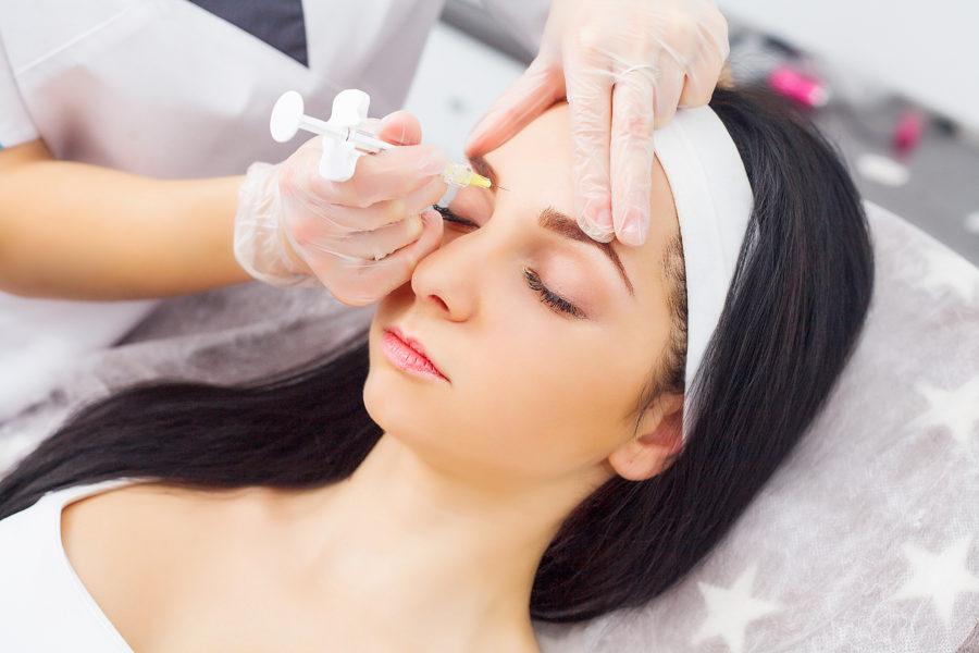 Mulher tendo toxina botulínica sendo aplicada em sua testa por meio de agulha